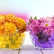 Beautiful flowers in vases with hydrogel on table on bright background — Stock Photo