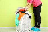 Woman with full laundry basket on green background — Stock fotografie