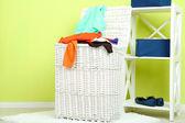 Full laundry basket  on wooden floor on  home interior background — Foto de Stock