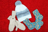 Winter cap, socks and gloves,  on color background — Stock Photo