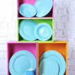 Beautiful  bright shelves and boxes with tableware  on  light wall background — Stock Photo #47348551