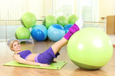 Young woman training with gymnastic ball in gym — Stock Photo