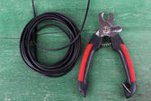 Side cutters cut cable on wooden background — Stockfoto
