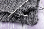 Knitting with spokes on wooden background — Stock Photo