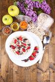 Healthy cereal with fruits on wooden table — Stock Photo