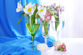 Freesias in glasses on table on fabric background — Стоковое фото