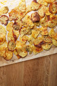Homemade potato chips on wooden table — Stock Photo