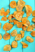 Homemade potato chips on color wooden table — Stock Photo
