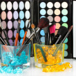 Make-up brushes in two glass cup with stones on palette of shadows background — Stock Photo #47394155
