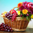 Composition with beautiful flowers in wicker basket and fruits,  on bright background — Stock Photo #47395213