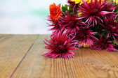 Beautiful flowers on wooden table,  on bright background — Stock Photo