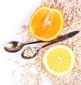 Fette di limone e di arancio con farina d'avena e cucchiai d'epoca isolati su bianco — Foto Stock