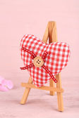 Beautiful heart  small decorative easel on pink background — Stock Photo