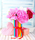 Beautiful flowers in colorful pencils vase on wooden background — Stock Photo