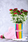 Beautiful flowers in colorful pencils vase on grey background — 图库照片