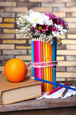 Beautiful flowers in colorful pencils vase on brick wall background — Stock Photo