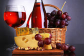 Pink wine, grapes and cheese on colorful background — Stock Photo