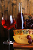 Pink wine, grapes and cheese on wooden background — Stock Photo
