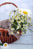 Beautiful bouquet of daisies in wicker basket on wooden background — Stock Photo