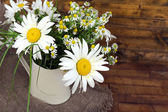 Beautiful bouquet of daisies in decorative vase on wooden background — Stock Photo