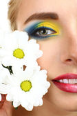 Beautiful woman with bright make-up and flower, close up — Stock Photo