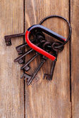 Magnet with old keys on wooden background — Stock Photo