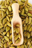 Green cardamom in wooden spoon close-up — Stock Photo