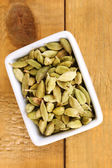 Green cardamom in white bowl on wooden background close-up — Stock Photo