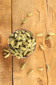 Green cardamom in ceramical bowl on wooden background close-up — Stock Photo