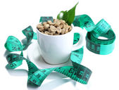 Raw green coffee beans in cup and measuring tape, isolated on white. Concept of weight loss — Stock Photo