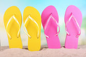 Bright flip-flops on sand, on nature background — Stock Photo