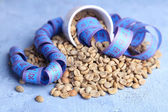 Raw green coffee beans and measuring tape, on color wooden background. Concept of weight loss — Stock Photo