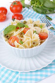 Delicious pasta with tomatoes on plate on table close-up — Stok fotoğraf