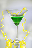 Glass of cocktail and streamer after party on gray background — Stock Photo
