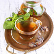 Composition of fresh mint tea in glass cup and teapot on tray, on wooden background — Stock Photo #47544385