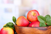Ripe sweet apples with leaves in wooden bowl on light background — Stok fotoğraf