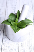 Fresh green mint in mortar on color wooden background — Stock Photo