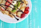 Läckra pannkakor med jordgubbar och choklad på tallriken på bordet — Stockfoto