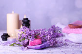 Composition with spa treatment, towels and lilac flowers — Stockfoto