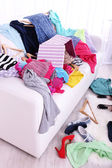 Messy colorful clothing on  sofa on light background — Stock Photo