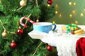 Santa holding mug and plate with cookies — Stockfoto