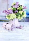 Composition with tea mugs and beautiful spring flowers in vase, on wooden table, on bright background — Стоковое фото