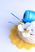 Colorful clews and crochet hooks in wicker basket on wooden background — Stock Photo