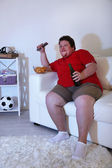 Lazy overweight male sitting on couch and watching television — Stock Photo