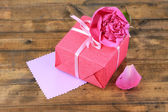 Pink gift with bow and flower — Stock Photo