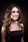 Beautiful young woman with long hair on dark brown background — Stock Photo
