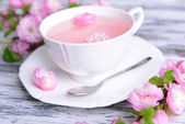 Beautiful fruit blossom with cup of tea on table close-up — Stock Photo