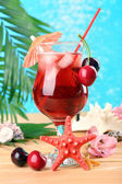 Refreshing cherry cocktail on beach table — Stock Photo