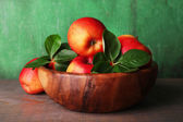 Ripe sweet apples with leaves in bowl on wooden background — Stock Photo