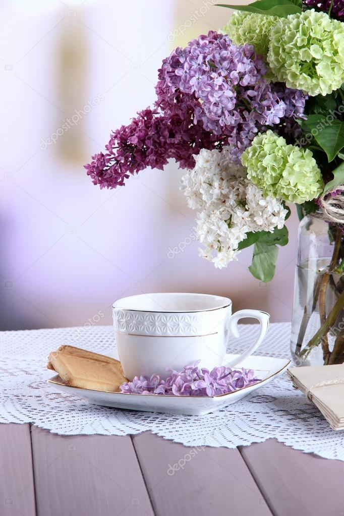Composition with cup of tea, old letters and beautiful spring flowers